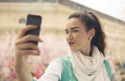 A jovem mulher à moda está tomando o selfie em seu telefone celular Foto de Stock