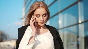 Jovem mulher à moda lindo em um equipamento elegante que passa o terminal de aeroporto e que fala no telefone tempo ensolarado vídeos de arquivo