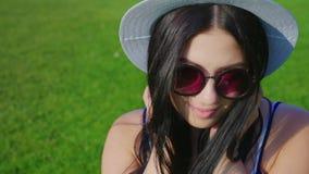 A jovem mulher à moda nos vidros olha na câmera a partir de baixo Retrato de uma mulher latino-americano atrativa filme