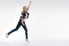Jovem mulher à moda que estica seu braço esquerdo Foto de Stock
