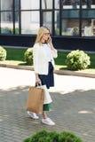 jovem mulher à moda que guarda sacos de compras e que fala pelo smartphone ao andar imagem de stock