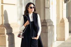 Jovem mulher à moda que olha lateral ao andar na rua fotos de stock