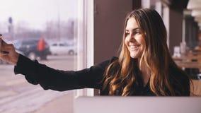 Jovem mulher à moda que senta-se no café e que toma o selfie com seu telefone esperto video estoque