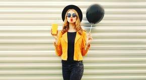 A jovem mulher à moda que tem o divertimento que funde os bordos vermelhos envia o beijo do ar fotografia de stock