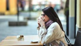 Jovem mulher à moda relaxado que aprecia a ruptura que bebe o café quente que senta-se no café na opinião lateral da rua filme