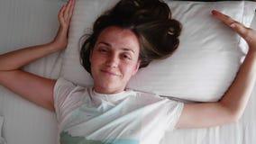 A jovem mulher é acordando, de esticão e de sorriso na cama na manhã