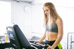 A jovem mulher é aptidão contratada no gym fotos de stock