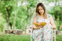 A jovem mulher ? livro de leitura exterior no jardim fotos de stock