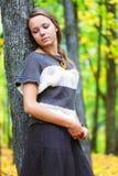 A jovem mulher é próxima ereto a árvore foto de stock royalty free