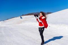 A jovem mulher é uma felicidade com a câmera no inverno Fotos de Stock Royalty Free