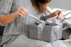 A jovem mulher abre a caixa com um presente de Natal imagens de stock
