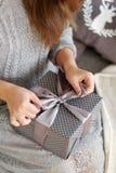 A jovem mulher abre a caixa com um presente de Natal foto de stock royalty free