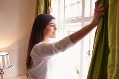 A jovem mulher abre cortinas para olhar a vista de uma janela imagens de stock royalty free