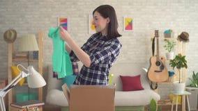 A jovem mulher abre felizmente uma caixa com um pacote