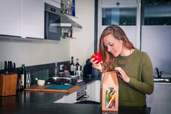 A jovem mulher abre um pacote de ingredientes frescos para o jantar saudável fotos de stock royalty free