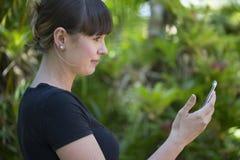 A jovem mulher admira o telefone celular novo foto de stock