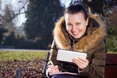 Jovem mulher/adolescente que usa o assento exterior da tabuleta no banco e Imagens de Stock
