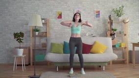 Jovem mulher afligida expressivo em medidas do sportswear seu peso nas escalas do assoalho filme