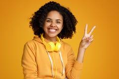 Jovem mulher afro-americano atrativa com sorriso brilhante vestida na roupa ocasional e nos fones de ouvido que mostram o gesto d imagem de stock