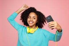 A jovem mulher afro-americano atrativa com sorriso brilhante vestida na roupa ocasional toma a imagem com smartphone sobre fotos de stock