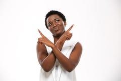 Jovem mulher afro-americano confusa que aponta acima com ambas as mãos Imagens de Stock