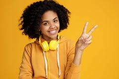 Jovem mulher afro-americano considerável com sorriso brilhante vestida na roupa ocasional e nos fones de ouvido que mostram o ges fotografia de stock