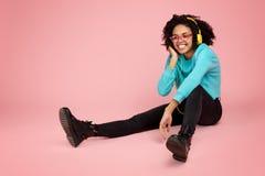 Jovem mulher afro-americano de encantamento com sorriso brilhante vestida na roupa ocasional, nos vidros e nos fones de ouvido es imagens de stock