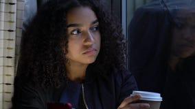 Jovem mulher afro-americano do adolescente da menina adolescente por uma janela usando seu telefone celular móvel para meios soci vídeos de arquivo
