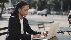 Jovem mulher afro-americano que trabalha no assento de assento do portátil no café no terraço do verão Negócio, trabalhando video estoque