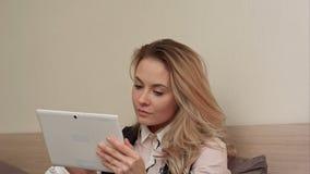 A jovem mulher agradável de sorriso usa uma tabuleta digital que faz a compra em linha que senta-se em uma cama em casa Foto de Stock Royalty Free