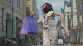Jovem mulher alegre bonito com sacos de compras A menina com fones de ouvido e telefone celular escuta a música ao dançar complet vídeos de arquivo