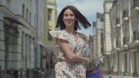 Jovem mulher alegre bonito com sacos de compras A menina com fones de ouvido e telefone celular escuta a música ao dançar complet filme