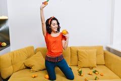 Jovem mulher alegre com cabelo moreno cortado no t-shirt alaranjado que tem o divertimento com as tangerinas no sofá no apartamen fotografia de stock royalty free