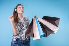 A jovem mulher alegre com fones de ouvido está comprando Foto de Stock