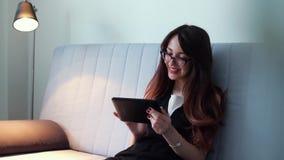 Jovem mulher alegre com o cabelo longo que senta-se no sofá e que usa o tablet pc vídeos de arquivo