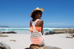 Jovem mulher alegre com o chapéu que senta-se pela praia imagens de stock