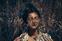 Jovem mulher alegre com os olhos fechados em um campo no portr do por do sol Imagens de Stock
