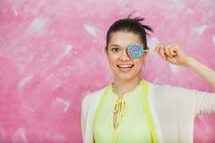 Jovem mulher alegre com os pirulitos coloridos sobre o backgroun cor-de-rosa Foto de Stock Royalty Free