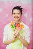 Jovem mulher alegre com os pirulitos coloridos sobre o backgroun cor-de-rosa Fotos de Stock Royalty Free