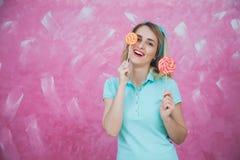 Jovem mulher alegre com os pirulitos coloridos sobre o fundo cor-de-rosa Fotografia de Stock Royalty Free