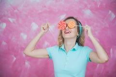 Jovem mulher alegre com os pirulitos coloridos sobre o fundo cor-de-rosa Fotos de Stock Royalty Free