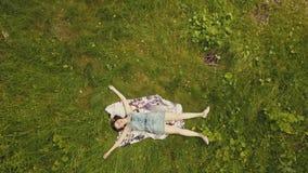 Jovem mulher alegre da opinião do céu na grama verde Menina bonita que relaxa na grama filme