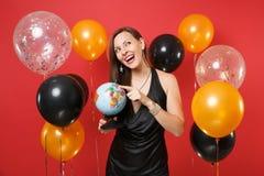 Jovem mulher alegre em pouco vestido preto que comemora guardando o globo do mundo, olhando acima, sonhando sobre a viagem em bri foto de stock