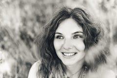 Jovem mulher alegre em um campo no por do sol Imagem de Stock Royalty Free