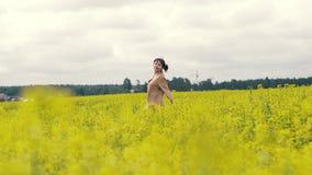 Jovem mulher alegre em uma caminhada do verão em um campo de flor filme