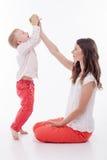 A jovem mulher alegre está alimentando sua criança fotografia de stock