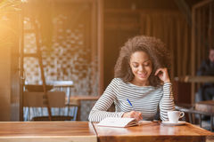 A jovem mulher alegre está escrevendo no caderno Imagens de Stock