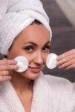 A jovem mulher alegre está tratando sua pele imagem de stock royalty free