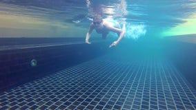Jovem mulher alegre feliz na série azul da natação na piscina, vista subaquática Câmera da ação video estoque