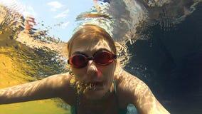 Jovem mulher alegre feliz na série azul da natação na piscina, vista subaquática Câmera da ação filme